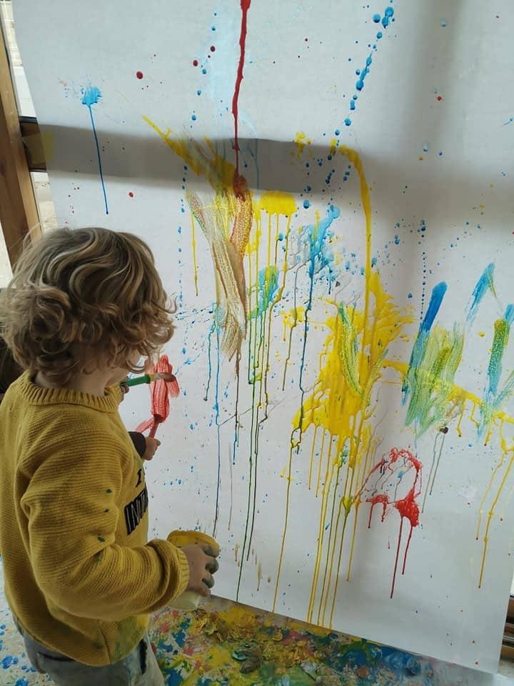 Niño jugando con pintura y lienzo